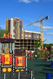 Khimki, Rusia - 30 de mayo 2017 Complejo del juego de niños en fondo de la construcción inferior en la orilla de Eco del parque Fotografía de archivo libre de regalías