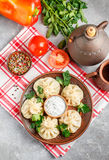 Khinkali - Georgian dumplings with meat and parsley. In a ceramic dish with a sauce of sour cream and greens. Selective focus royalty free stock images