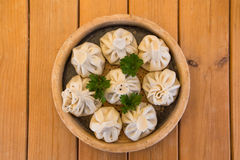Khinkali on a plate on a wooden table. Traditional Georgian cuisine. cuisine of the Georgian people.  Stock Image