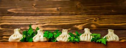 Khinkali su una tavola di legno con le verdure Fotografia Stock