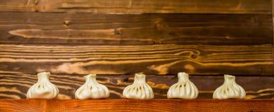 Khinkali su una tavola di legno con le verdure Immagini Stock