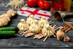 Khinkali su una tavola di legno con le verdure Immagine Stock