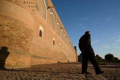 Old man walking at sunset in the old town. Itchan Kala. Khiva. Uzbekistan royalty free stock images
