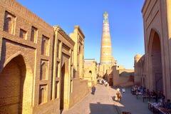 KHIVA, USBEKISTAN - 6. MAI 2011: Eine Gasse innerhalb alter Stadt Khiva mit dem Islam Khodja-Minarett im Hintergrund Stockbild
