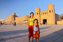 KHIVA UZBEKISTAN - MAJ 6, 2011: Två uzbekiska små flickor som framme poserar av stadsväggarna av Khiva på solnedgången Royaltyfri Foto