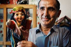 Man showing puppets in his workshop in traditional dress royalty free stock image