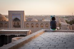 A lonely tourist sitting on the roof of one of houses in Old City of Khiva stock photos