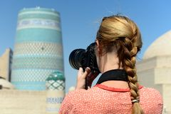 Khiva, Uzbekistan, Silk Route. Khiva, Uzbekistan, Tourist on the main square  is photographing ancient monuments of Khiva of architectural pearl on the Silk stock image