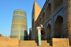 Khiva, Uzbekistan, Silk Route. Khiva, Uzbekistan, Tourist on the main square  is photographing ancient monuments of Khiva of architectural pearl on the Silk stock images