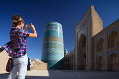 Khiva. Young lady taking a picture of oriental buildings in Itchan Kala ancient town. Khiva, Uzbekistan royalty free stock photography