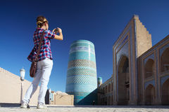Khiva. Young lady taking a picture of oriental buildings in Itchan Kala ancient town. Khiva, Uzbekistan royalty free stock images