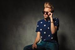 Kühlen Sie die Mode ab, die seine Sonnenbrille beim Sitzen hält Stockfoto
