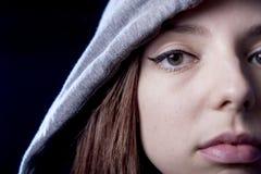 Kühles Jugendlichmädchen oder junge Frau auf ihrem 20s, das an kühle darstellende tragende Haube der Haltung aufwirft Lizenzfreies Stockfoto