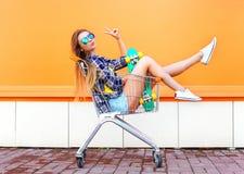 Kühles Mädchen der Mode, das Spaß im Einkaufslaufkatzenwarenkorb mit Skateboard hat Lizenzfreie Stockfotos