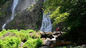 Khlong lan waterfall with people are relaxing, natural tourist attraction in Kampang Phet province ,Thailand. stock video