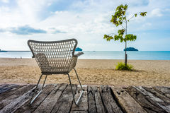 Khlong Wan beach with silhouette of wicker chair on wooden log d Stock Images