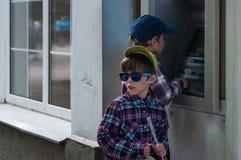 KHMELNITSKY, UCRÂNIA - 29 DE JULHO DE 2017: Dois irmãos perto do ATM Fotografia de Stock Royalty Free