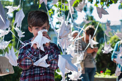 KHMELNITSKY, UKRAINE - JULY 29, 2017: Happy little boy standing. KHMELNITSKY, UKRAINE - JULY 29, 2017: Happy little boy surrounded by paper birds. Origami crane Royalty Free Stock Photo