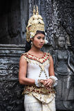 Khmer apsara dancer next to stone dancer statue. SIEM REAP, CAMBODIA - DECEMBER 28, 2008: Khmer classical dancer  in full traditional costume stands next to a Stock Photography