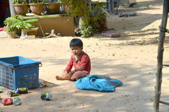 Khmer little boy tired of playing crumpled cans of drinks under Royalty Free Stock Photo