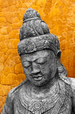 Khmer Style Statue. A cast Khmer style statue against an orange clay wall stock photography