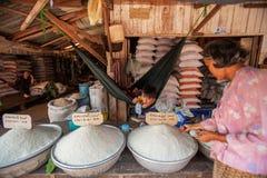 Khmerjunge liegt in einer H?ngematte, die wartet, um Langkornreis am lokalen Markt zu verkaufen Dong Tong Market, Koh Kong, Kambo stockfoto