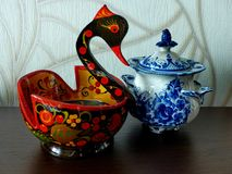 Khokhloma bucket in the form of a bird and sugar bowl Gzhel. Things in Russian traditional Khokhloma and Gzhel style. Royalty Free Stock Photo