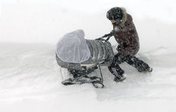 Kholmsk,库页岛,俄罗斯联邦, 1月7日2015父亲未认出与在漂泊的一辆婴儿车 库存图片