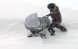 Kholmsk Sakhalin ö, rysk federation, 7 Januari 2015 fader som är oidentifierad med en barnvagn i drivorna Arkivbilder