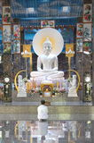 Khon Kaen, Thailand - August 02, 2017 : Asian Buddhist woman wearing white dress sitting and paying respect to big white Buddha s royalty free stock photo