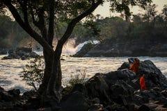 Khone Phapheng Falls At Sundown With Buddhist Monks Enjoying The Surroundings, Si Phan Don, Champasak Province, Laos Royalty Free Stock Image