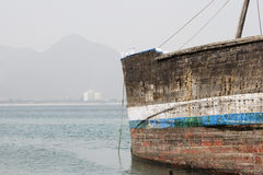 Khor Fakkan UAE old wooden dhow washed up on shore in front of Khor Fakkport Royalty Free Stock Image