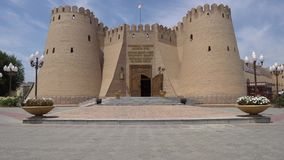 Khujand Sughd Region Historical Museum. Frontal Main Gate Entrance View with Waving Tajikistan Flag on a Sunny Blue Sky Day stock video footage