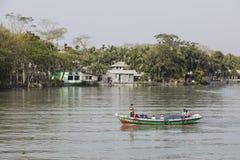 Khulnâ, Bangladesh, le 1er mars 2017 : Petites feuilles de ferry-boat transportant des passagers devant un village Image libre de droits