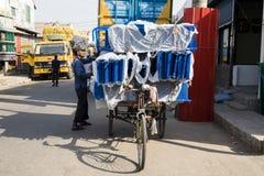 Khulna, Bangladesh, el 28 de febrero de 2017: El conductor de Trishaw carga su vehículo con las mercancías Imagenes de archivo