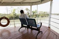 Khulna, Bangladesh, el 1 de marzo de 2017: El hombre se sienta en el arco de un transbordador de pasajero Imagen de archivo libre de regalías