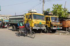 Khulna, Bangladesh, February 28 2017: Trishaw Driver drives in Khulna. In front of a truck in the street Stock Photos