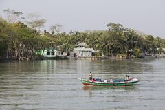 Khulna, Bangladesh, March 1 2017: Small passenger ferry leaves in front of a village. That lies by the river Royalty Free Stock Image