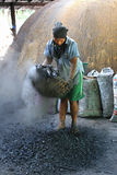 Khunpepe040. Nakhon Si Thammarat, Thailand - June 12, 2012 : A worker sifts through charcoal pieces. Separating small pieces before packing into a bag for sell Stock Photography