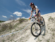 KHVALYNSK - MAY 7, 2016: Female cyclist rides at XCE eliminator track championship 'Match of Russian cities'. KHVALYNSK - MAY 7, 2016: Female cyclist descends Stock Photos