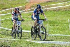KHVALYNSK - 7 MEI, 2016: Twee vrouwelijke fietsersrit bergopwaarts bij XCE-het kampioenschap &#x27 van het eliminatorspoor; Gelij Royalty-vrije Stock Afbeelding