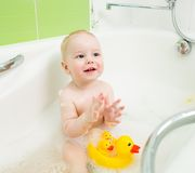 Ki clapping hands and smiling while taking a bath Royalty Free Stock Photography