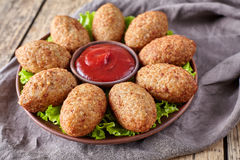 Kibbeh traditional middle eastern homemade beef, lamb, goat or camel meat stuffed bulgur kofta. Spicy meatball croquettes on green salad food on vintage wooden Stock Images