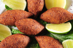 Kibe. Fried kibe with lemon and lettuce Royalty Free Stock Image