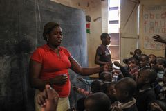 African volunteer teacher in the poorest school in Kibera royalty free stock image