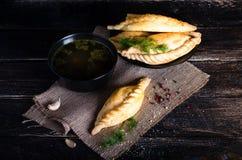 Kibinai, kybyn, kybynar, cheburekki - le pasticcerie tradizionali hanno riempito di montone su fondo di legno scuro lithuania lib immagini stock