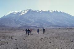 Kibo Peak. Trekkers walk across the alpine desert towards the base of Kibo Peak on Mount Kilimanjaro stock image