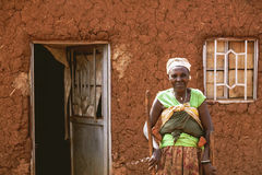 KIBUYE, ΡΟΥΆΝΤΑ, ΑΦΡΙΚΉ - 11 ΣΕΠΤΕΜΒΡΊΟΥ 2015: Άγνωστη γυναίκα Εξετάζει τη κάμερα μπροστά από το χωμάτινο σπίτι της Στοκ εικόνες με δικαίωμα ελεύθερης χρήσης