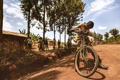 KIBUYE, RUANDA, AFRÄ°CA - 11. SEPTEMBER 2015: Nicht identifizierter Junge Der afrikanische Junge auf Schotterweg mit seinem Fahrr Stockbilder