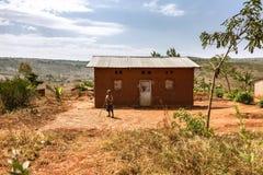 KIBUYE, RUANDA, AFRIKA - 11. SEPTEMBER 2015: Unbekanntes Kind Das Haus des kleinen Landwirt African-Jungen Lizenzfreie Stockfotos